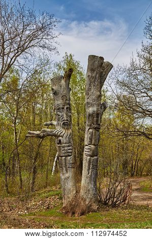 SARATOV, RUSSIA - MAY 1, 2015: Two idols cut out from a tree stand in the wood