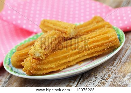 Freshly made Spanish churros on plate with pink cloth in the background