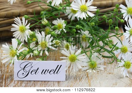 Get well card with fresh chamomile flowers on rustic wooden surface