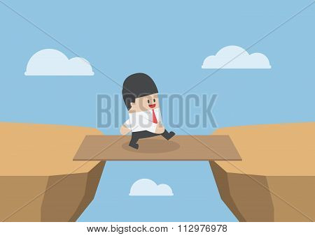 Businessman Cross The Cliff Gap By Wooden Board As A Bridge