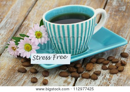 Stress free card with cup of coffee and pink daisies on rustic wooden surface
