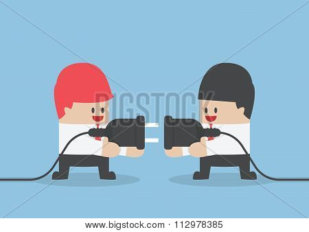 Two Businessman Trying To Connect Electric Plug Together