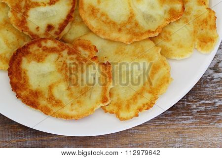 Traditional potato fritters on white plate, closeup
