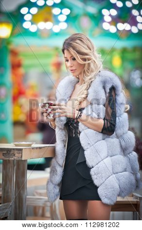 Elegant long fair hair young beautiful woman with white fur coat, outdoor shot in a cold winter day.