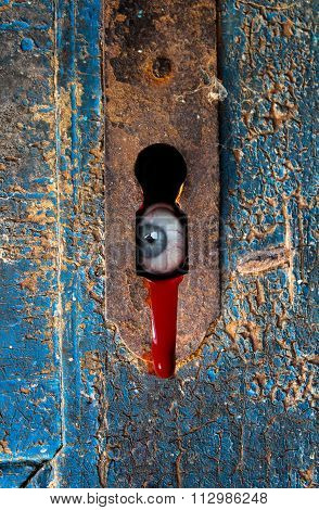 Eyeball Staring Through Rusty Keyhole