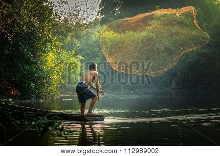 Asian Fisherman Fishing By Net For Fish In River