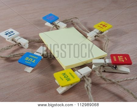 Yellow Sticky Paper With Wooden Paper Clips As Business Days