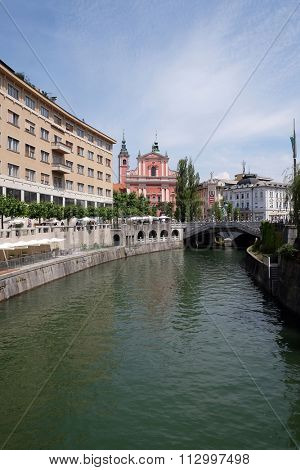LJUBLJANA, SLOVENIA - JUN 30: Franciscan Church of the Annunciation and Triple Bridge on the Ljubljanica River in Ljubljana, Slovenia on Jun 30, 2015