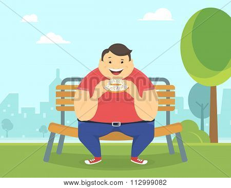 Happy fat man eating a big donut in the park