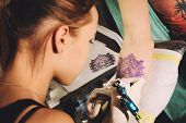 Постер, плакат: Girl tattoo artist makes tattoo on a hand against purplish blue likeness of a future tattoo using a