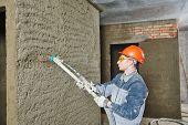 Plasterer operating sprayer equipment machine for spraying thin-layer putty plaster finishing on bri poster