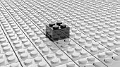 Connected white lego blocks with one black standing out, abstract background. poster