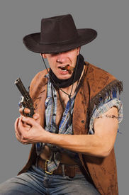 picture of wild west  - cowboy with revolver isolated on grey background - JPG