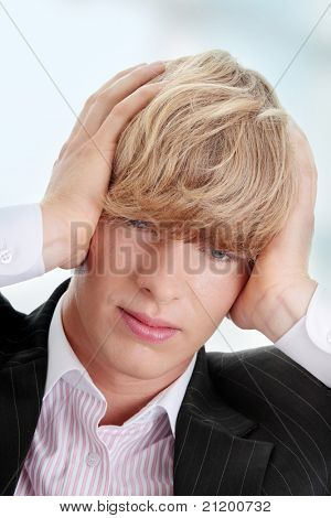 Young businessman with headache.