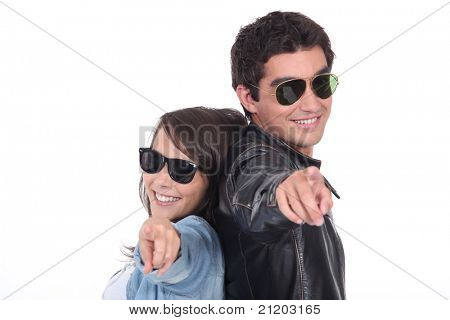Cool young couple in sunglasses pointing at the camera
