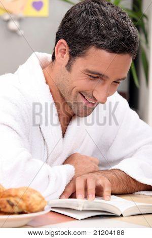 smiling man in robe reading