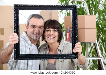 a couple is holding and posing behind a painting frame inside an apartment full of unpacked packages