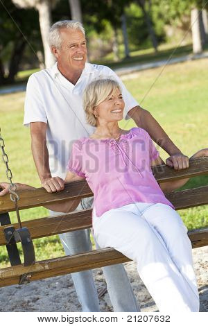 Happy senior man and woman couple together outside in sunshine on a park swing