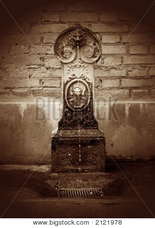 Sepia Toned Image Of Small Fountain Against A Brick Wall In Venice, Italy, With Added Film Grain Eff