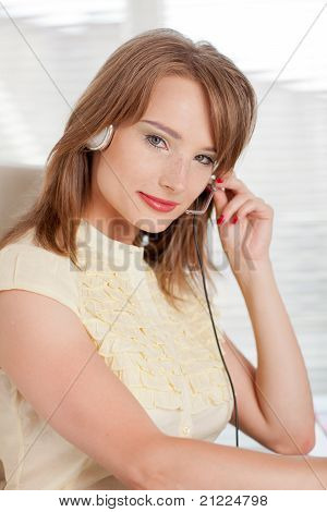 Young Businesswoman In Earphones At The Office.