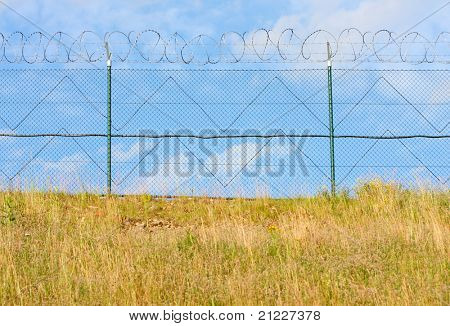 Fence with a barbed wire, close up with shallow DOF.