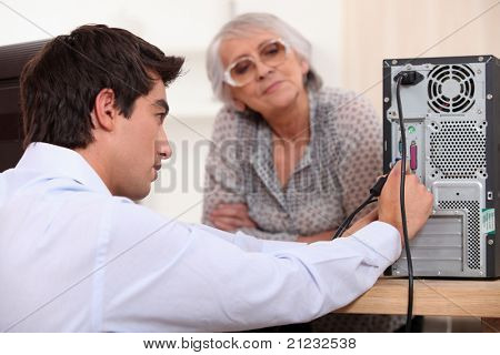 young man wearing a shirt is plugging cables on the back of a computer, an old woman is watching him