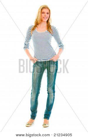 Retrato de cuerpo entero de niña adolescente hermosa sonriente con las manos en los bolsillos de los pantalones vaqueros aislados en blanco