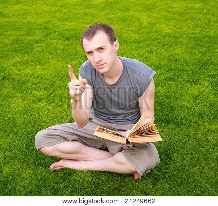A Young Man Reading A Book On The Grass
