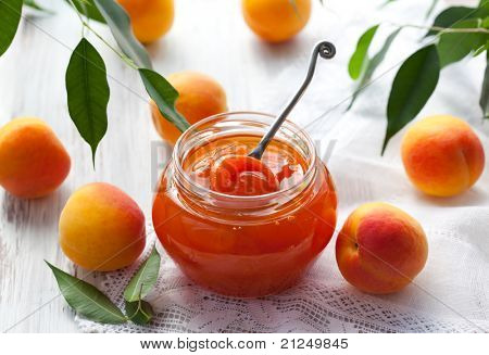Apricot jam in jar and fresh fruits with leaves