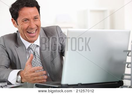 Man laughing hysterically at his laptop computer