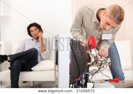 female technician repairing a television