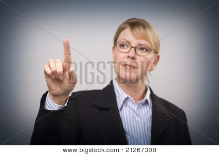 Businesswoman Reaching Out with Finger - Ready for Your Own Buttons or Touch Screen - Focus is On Her Finger.