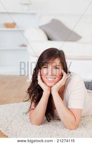 Attraktive Brünette Frau posiert beim liegen auf einem Teppich