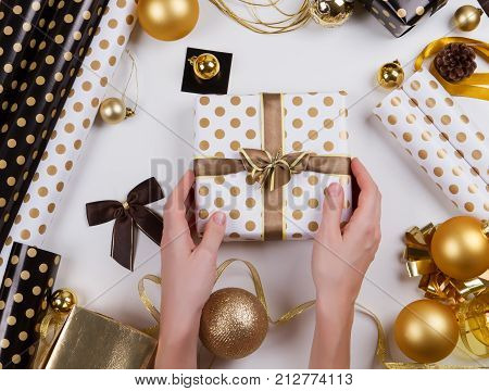 poster of woman hand packaging christmas gift box. Process of package new year gift box. Christmas packaging wrapping paper, ribbon, twine, bow and thread, scissors on wooden background