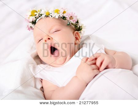 Portrait of a yawning baby girl on a light background with a wreath of flowers on her head
