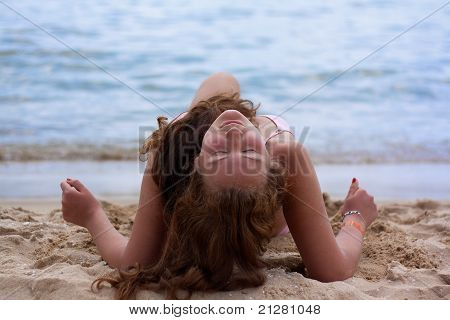 A Pretty Woman In Bikini Sunbathing At The Beach