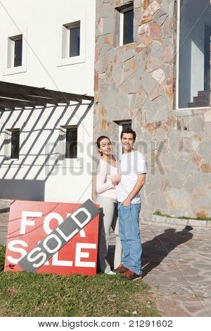Couple standing near house sold sign outside home
