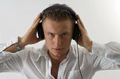 picture of partially clothed  - A caucasian man listening to headphones music with a white background - JPG