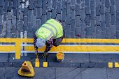 stock photo of hse  - Workman hand painting double yellow lines on cobbled street - JPG