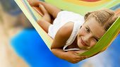 Beautiful teenager girl relaxing in the hammock on tropical beach with turquoise sea water, hot sunn poster