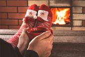 Teens Hands Hold A Red Cup Of Coffee In Front Of The Fireplace. Christmas Holiday. poster