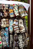 Knitted Gloves And Socks With Colorful Ornaments For Sale On The Market poster