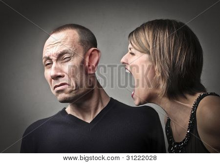 Angry woman screaming against her husband with his face deformed by the power of the scream
