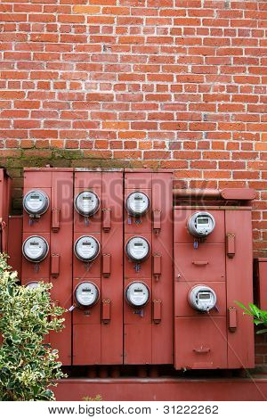 Ten Electric Meters on the red brick wall of an apartment building