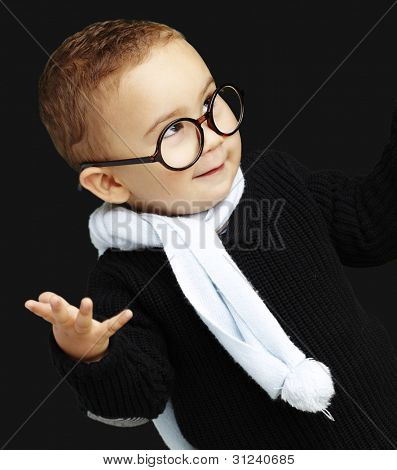 portrait of adorable kid gesturing doubt against a black background