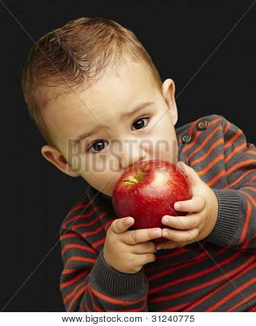 portrait of a handsome kid sucking a red apple over black background