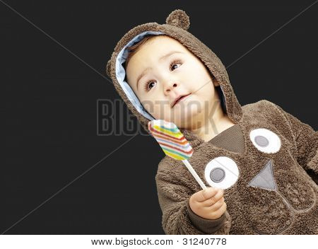 portrait of a handsome kid wearing a brown bear sweatshirt holding a candy