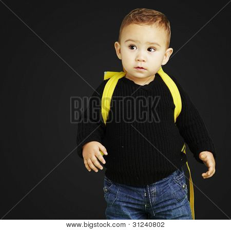 portrait of adorable kid carrying yellow backpack over black background