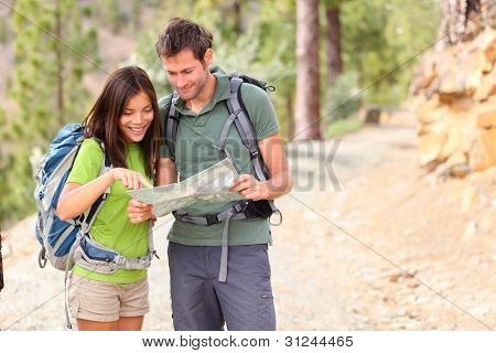hiking - hikers looking at map. Couple or friends navigating together smiling happy during camping travel hike outdoors in forest. Young mixed race Asian / Caucasian woman and Caucasian man.