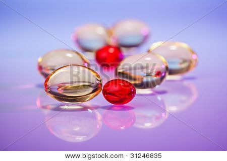 Pills (capsules) of cod-liver oil on violet, macro view with selective focus